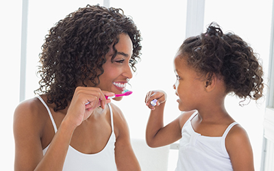 A mother and child brushing their teeth together
