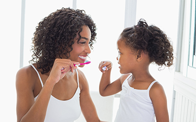 A mother brushing her teeth with her daughter before bed
