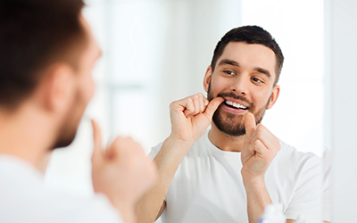 Handsome man flossing in front of mirror